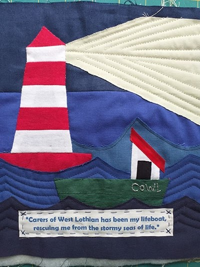 A Quilted square showing a boat called COWL on the sea near a lighthouse
