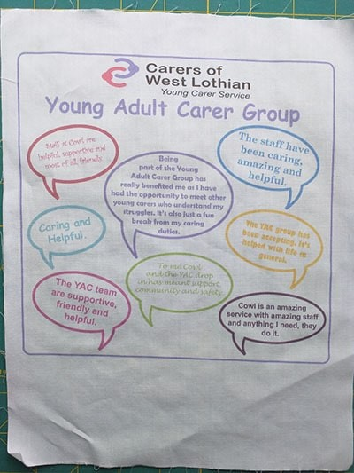A piece of fabric with coloured young adult carer quotes in speech bubbles printed onto it